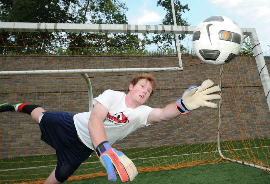 Greenwich High School goalie Emmett Clarke makes a stop during soccer practice at the school, Friday, Sept. 7, 2012. Clarke is co-captain of the team with Pieter Zenner. Photo: Bob Luckey / Greenwich Time