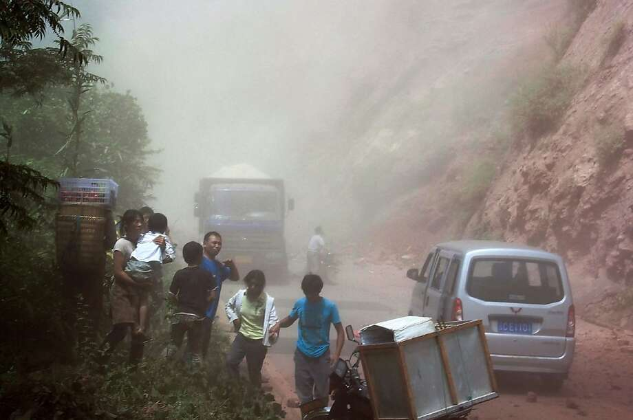 People run as rocks fall near their vehicles after the area was hit by an earthquake in Zhaotong town, Yiliang County, southwest China's Yunnan Province, Friday, Sept. 7, 2012. A series of earthquakes collapsed houses and triggered landslides Friday in a remote mountainous part of southwestern China where damage was preventing rescues and communications were disrupted. Dozens of deaths have been reported. (AP Photo) CHINA OUT Photo: Associated Press