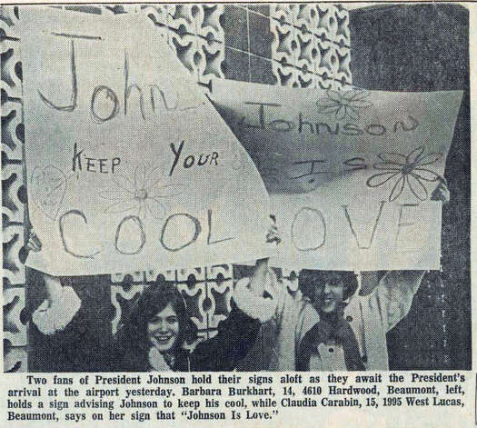 Fans of Lyndon Johnson's hold up signs while waiting for Johnson's arrival at the airport.   Enterprise File photo