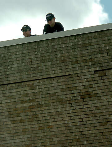 Swat teams keep an eye on the crowd from a rooftop on Orleans Street outside at the Julie Rogers Theater in Beaumont, TX Thursday, February 28, 2008 as they wait for the arrival of Presidental candidate, Barack Obama. Beaumont Enterprise, Tammy McKinley Photo: TAMMY MCKINLEY