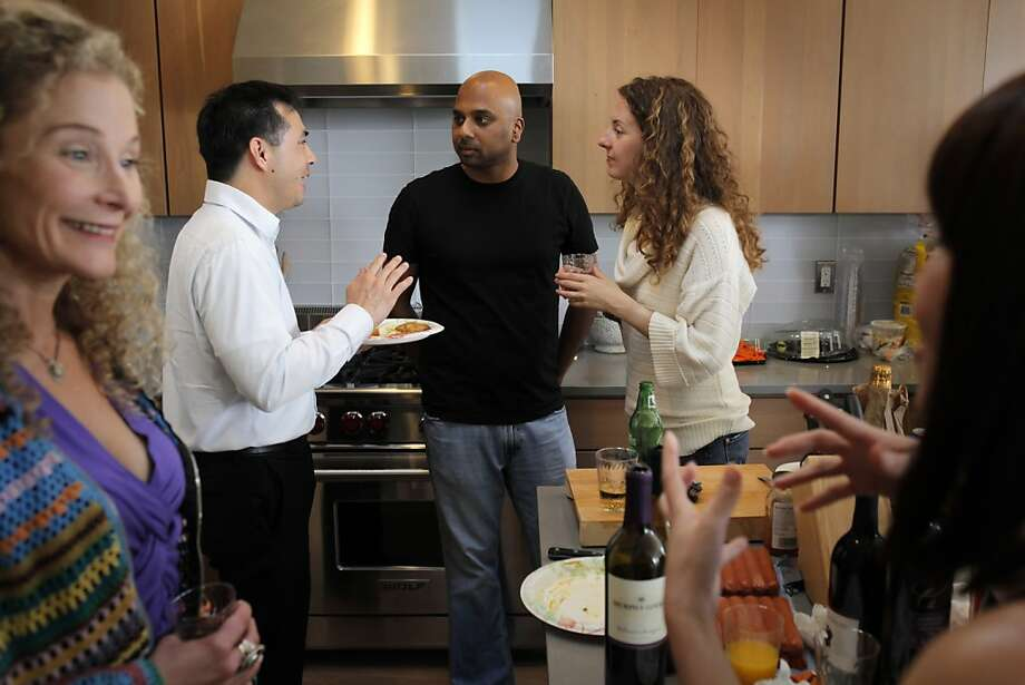 Anant Sapatnekar (center) talks with guests Albert Lou and Elena Zehr at the housewarming party for his new condo in Bernal Heights. Sapatnekar, a native of India, took a job in San Francisco after spending 16 years in Canada. Photo: Carlos Avila Gonzalez, The Chronicle