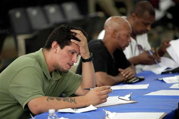 FILE - In this Tuesday, Aug. 21, 2012 file photo, job seekers fill out applications at a construction job fair in New York. U.S. employers added 96,000 jobs last month, the Labor Department said Friday, Sept. 7, 2012, a weak figure that could slow any momentum President Barack Obama hoped to gain from his speech to the Democratic National Convention. (AP Photo/Seth Wenig, File) Photo: Seth Wenig, AP / AP