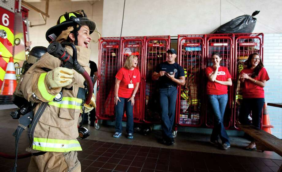 Martha Barrera of H.E.B., jokes with her co-workers as she takes a turn wearing firefighter gear after she and her co workers made breakfast for the firefighters of Houston Fire Department's Station Six, Friday, Sept. 7, 2012, in Houston. More than 3,000 H-E-B employees from 300 H-E-B stores lent a helping hand to firefighters across Texas as part of the company wide volunteer service project Helping Heroes. This community service project honors September 11th as a National Day of Service and Remembrance that pays tribute to the men and women rescue teams who risked and lost their lives at the World Trade Center. Photo: Nick De La Torre, Houston Chronicle / © 2012  Houston Chronicle