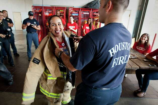 Martha Barrera of H.E.B. tries on fire gear after she and her co workers made breakfast for the firefighters of Houston Fire Department's Station Six, Friday, Sept. 7, 2012, in Houston. Photo: Nick De La Torre, Houston Chronicle / © 2012  Houston Chronicle