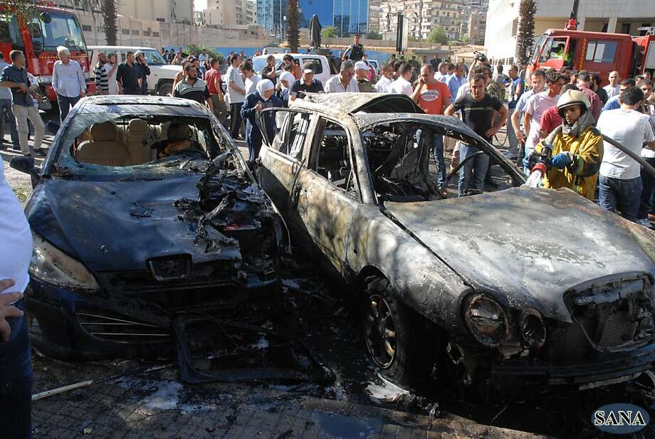 A firefighter douses cars destroyed by a bombing near the Information and Justice ministries. Photo: Hopd, Associated Press