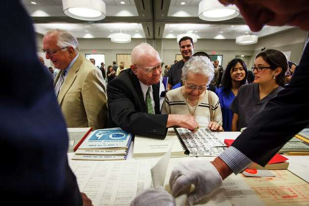 Marvin Bennack, center, and his wife Marge look through old dental school graduation photos from when Marvin attended school after the pictures and other memorabilia were opened from a sealed 1500 lb marble time capsule from 1954. Photo: Michael Paulsen, Houston Chronicle / © 2012 Houston Chronicle