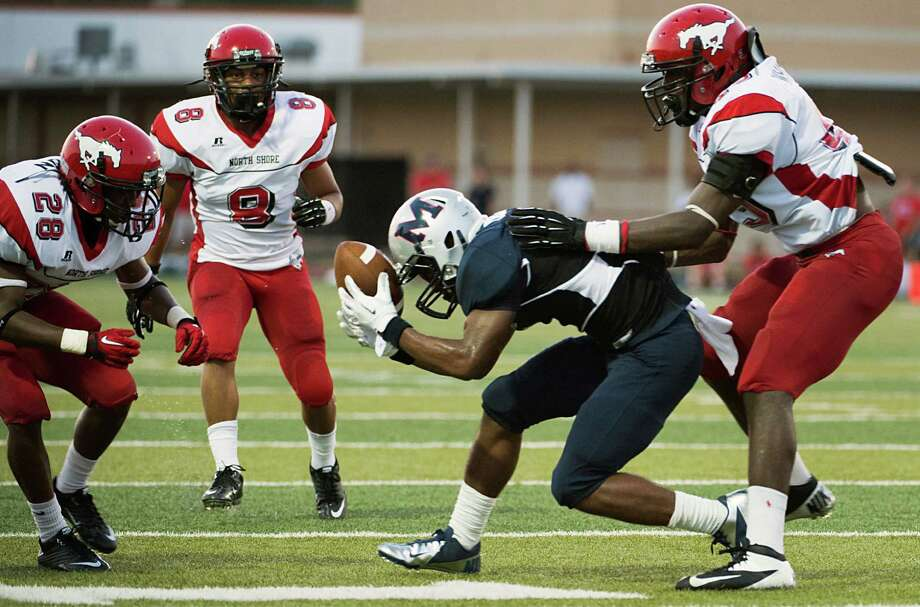 Manvel receiver Carlos Thompson tries to hold onto a pass as North Shore's Darius Mouton (28) and Zac Whitley (45) defend during the first quarter of a high school football game on Friday, Sept. 7, 2012, in Alvin. Photo: Smiley N. Pool, Houston Chronicle / © 2012  Houston Chronicle