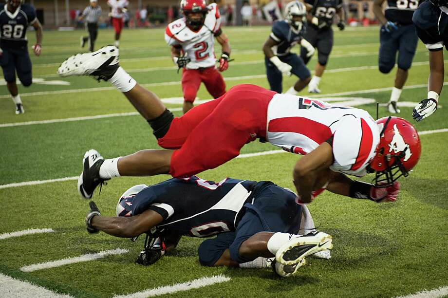 North Shore running back Tristan Houston is upended by Manvel cornerback Gary Haynes during the first quarter of a high school football game on Friday, Sept. 7, 2012, in Alvin. Photo: Smiley N. Pool, Houston Chronicle / © 2012  Houston Chronicle