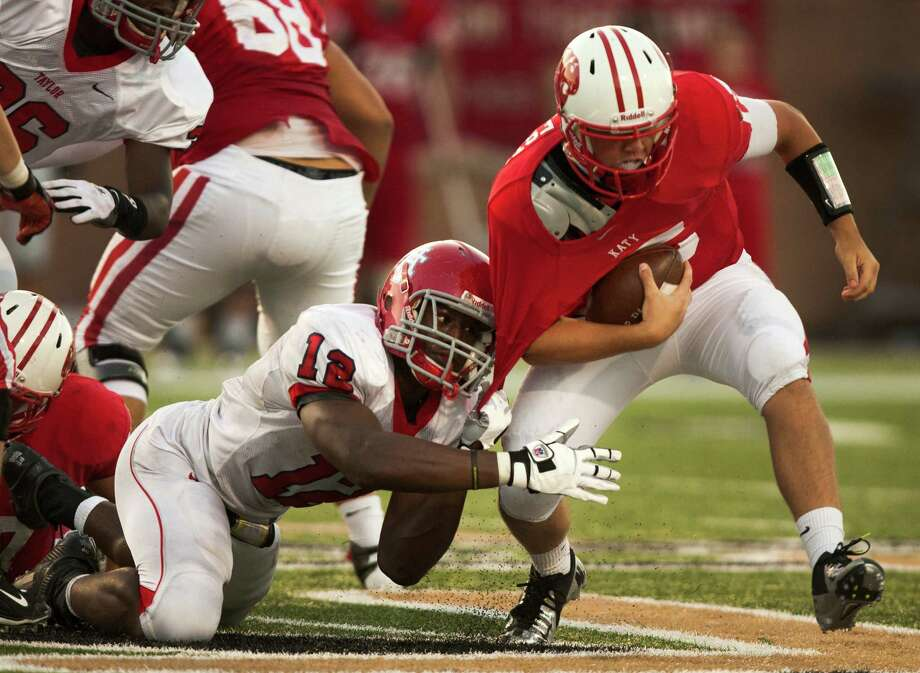 Katy quarterback Kiley Huddleston (15) is brought down by Alief Taylor defensive lineman Obo Okoronkwo (12) during the first half at Rhodes Stadium on Friday, Sept. 7, 2012, in Katy. Photo: J. Patric Schneider, For The Chronicle / © 2012 Houston Chronicle