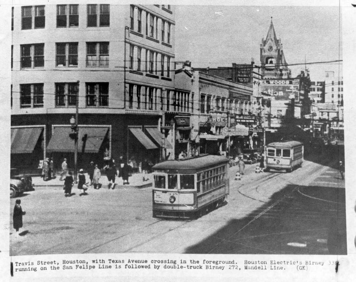 Two streetcars make their way down Travis Street in an old photo of downtown Houston. Texas Avenue is the cross street in the foreground.