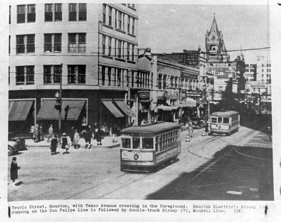 Two streetcars make their way down Travis Street in an old photo of downtown Houston. Texas Avenue is the cross street in the foreground. / handout copy shot