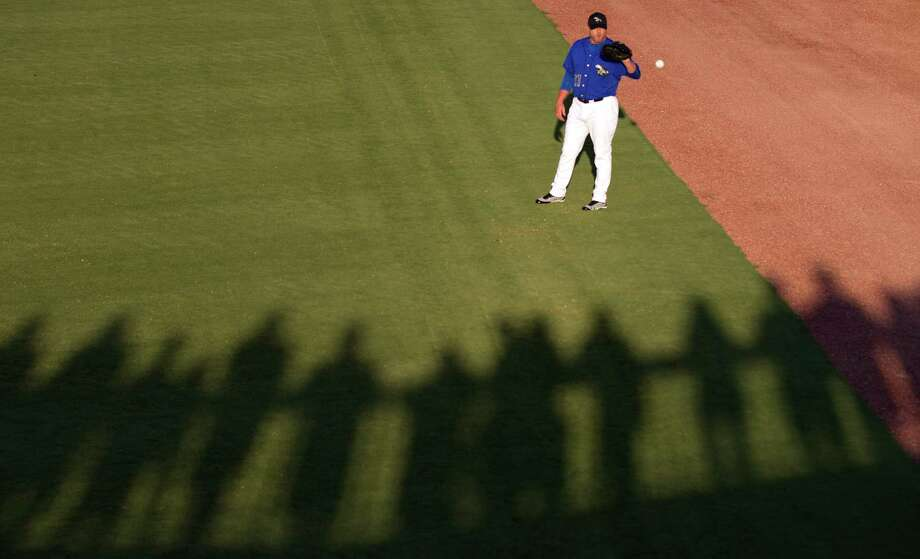 Sugar Land Skeeters fans cast shadows on the field as starter Roger Clemens warms up in the outfield before a minor league baseball game against the Long Island Ducks at Constellation Field Friday, Sept. 7, 2012, in Sugar Land. Photo: Brett Coomer, Chronicle / © 2012 Houston Chronicle