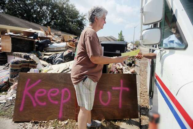 Marie Hauser receives her mail outside her flooded home on September 6, 2012 in LaPlace, Louisiana. Louisiana officials estimate that at least 13,000 homes were damaged by Hurricane Isaac. Louisiana officials estimate that at least 13,000 homes were damaged by Hurricane Isaac. Photo: Mario Tama, Getty Images / 2012 Getty Images