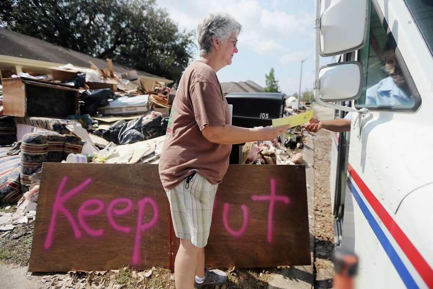 Marie Hauser receives her mail outside her flooded home on September 6, 2012 in LaPlace, Louisiana.