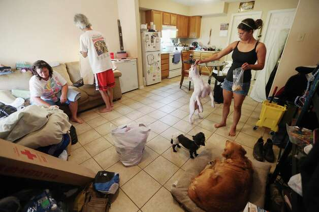 Melanie and Philip Martinez Sr. go through donated clothes as daughter Kala Martinez plays with family dogs in Kala's one bedroom apartment on September 7, 2012 in Chalmette, Louisiana. Melanie, along with her husband and mother, are staying in Kala's apartment for the time being after their home in Braithwaite flooded during Hurricane Isaac. It was the fifth home Martinez has had destroyed due to hurricanes in Louisiana. Photo: Mario Tama, Getty Images / 2012 Getty Images