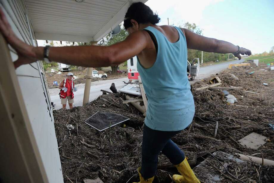 "Gina Hunter steps out of her home which washed onto a levee to collect water from Red Cross worker Donna McNeil in Plaquemines Parish on September 7, 2012 in Braithwaite, Louisiana.  Hunter said, ""I never expected to have the levee as my backyard."" Louisiana officials estimate that at least 13,000 homes were damaged by Hurricane Isaac. Photo: Mario Tama, Getty Images / 2012 Getty Images"