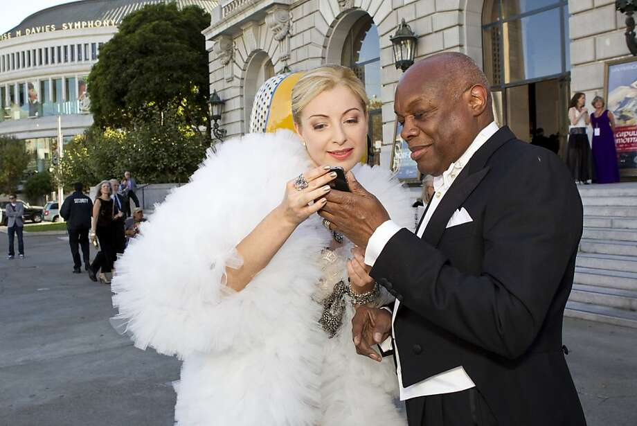 Sonya Molodetskaya looks over cell phone photos taken by a friend with former San Francisco Mayor Willie Brown after arriving at the San Francisco Opera Opening Night Gala at War Memorial Opera House in San Francisco, Calf., on Friday, September 7, 2012. Photo: Laura Morton, Special To The Chronicle