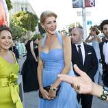 Brenda Zarate (left) and designer Karen Caldwell (center) arrive at the San Francisco Opera Opening Night Gala wearing gowns designed by Caldwell at War Memorial Opera House in San Francisco, Calf., on Friday, September 7, 2012.
