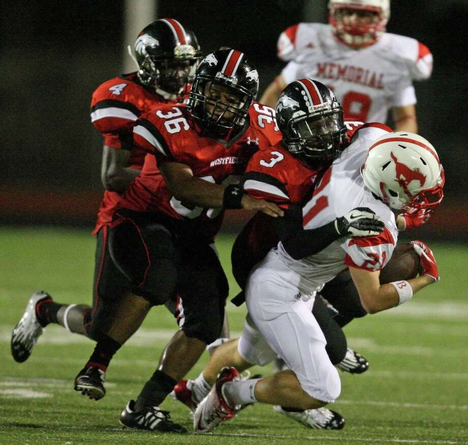 Memorial's Chris Beggins (21) is tackled by Westfield's Brian Peavy (4), Luis Sanchez (36) and Goldie Jones (3) during the second half of a high school football game, Friday, September 7, 2012 at George Stadium in Spring, TX. Photo: Eric Christian Smith, For The Chronicle
