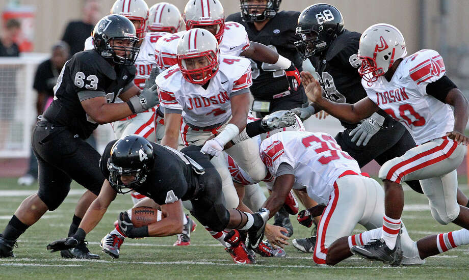 Knight running back Justin Stockton slips through the heap of lineman as Steele hosts Judson at Lehnhoff Stadium on September 7, 2012. Photo: Tom Reel, Express-News / ©2012 San Antono Express-News