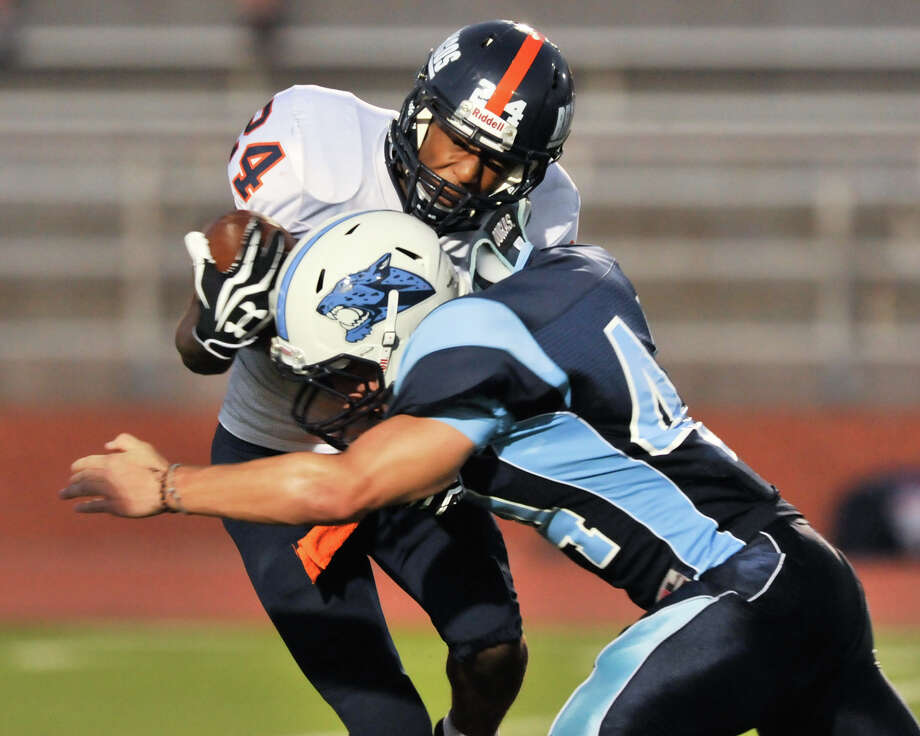 Brandeis' William Hughes (24) is stopped by Johnson's Darian King. Photo: ROBIN JERSTAD  ROBIN@JERSTADPHOT, Express-News