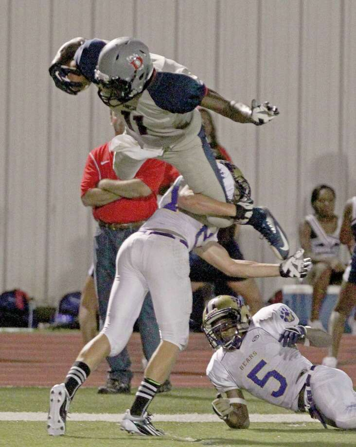 9/7/12: Dawson's Tony Upchurch #11 is upended by Montgomery's Clint Ivy #21 at the RIG in Pearland, Texas. Photo: Thomas B. Shea, For The Chronicle / © 2012 Thomas B. Shea
