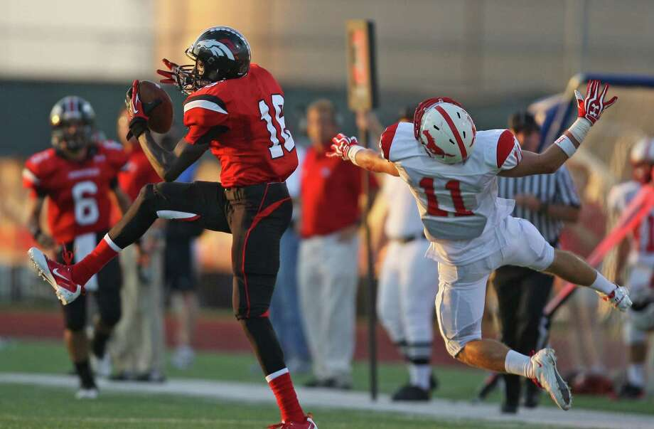 Westfield's Tyler Batson (left) makes a reception past Memorial's David Holland during the first half of a high school football game, Friday, September 7, 2012 at George Stadium in Spring, TX. Photo: Eric Christian Smith, For The Chronicle
