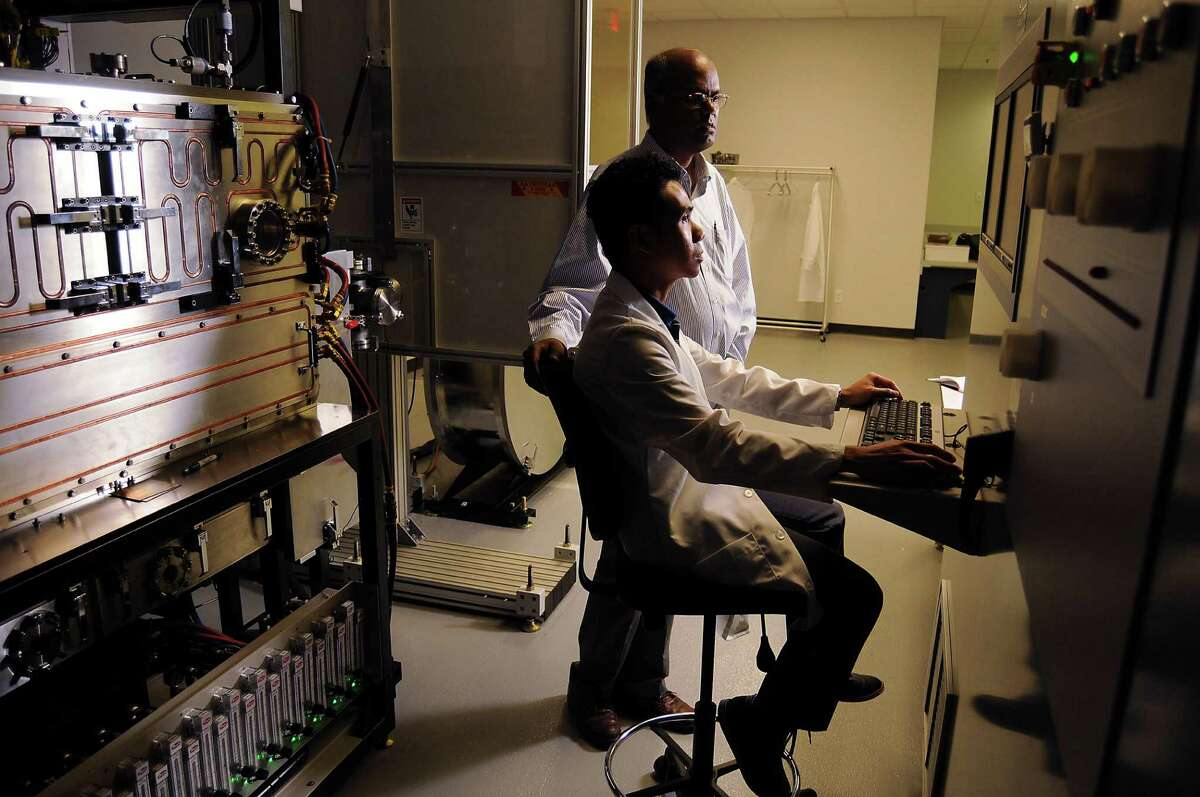 Venkat Selvamanickam, standing, director of the Applied Research Hub, talks with SuperPower employee Albert Guevara at a machine that produces superconducting wire at the University of Houston's Energy Research Park.