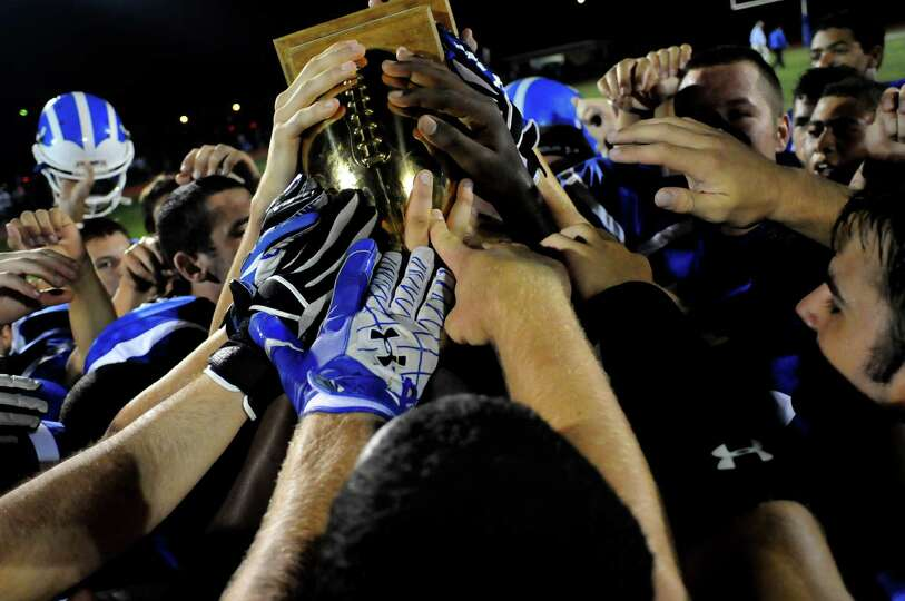 Shaker's football team touches the Town of Colonie Cup after winning 40-8 over Colonie on Friday, Se