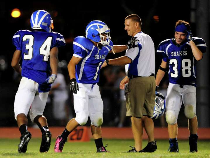 Shaker's football players celebrates with coach Greg Sheeler after winning 40-8 over Colonie on Frid