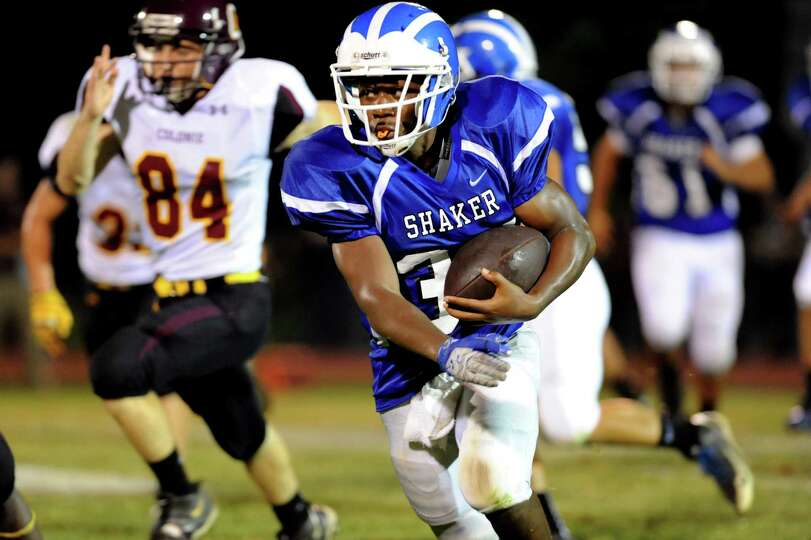 Shaker's Kenny Jackson (34), center, runs the ball during their football game against Colonie on Fri