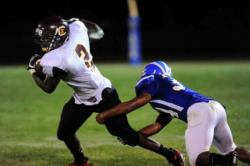 Colonie's Kevon Johnson (2), left, tries to break a tackle from Shaker's Kenny Jackson (34) during t