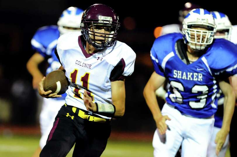 Colonie's quarterback Eugene Kupiec (11), left, runs the ball during their football game against Sha