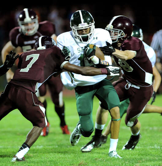 Schalmont's Chas Higgins (15), center, runs into tough defense l during their football game against
