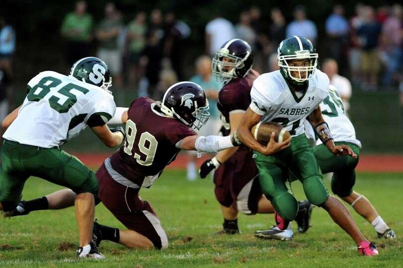 Schalmont's quarterback Devon Willis (21), right, runs runs the ball during their football game agai