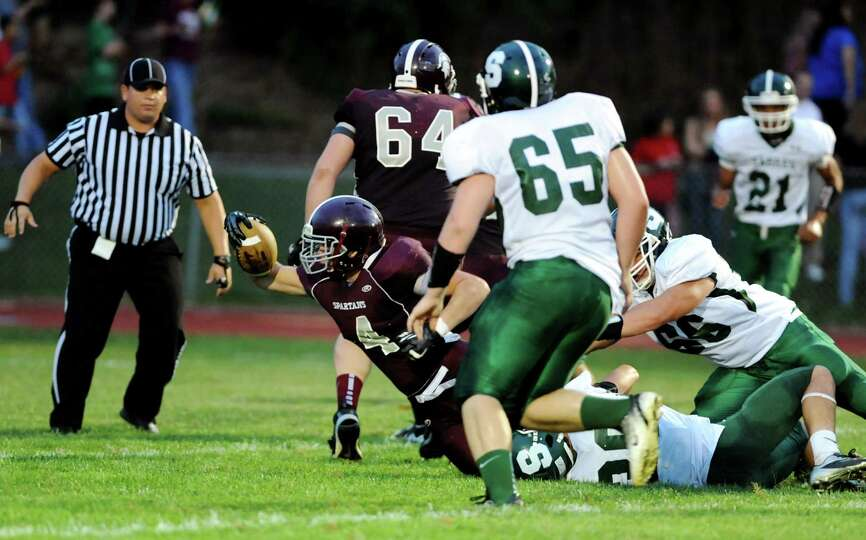 Burnt Hills Dan Porter (4), left, reaches for extra yardage during their football game against Schal