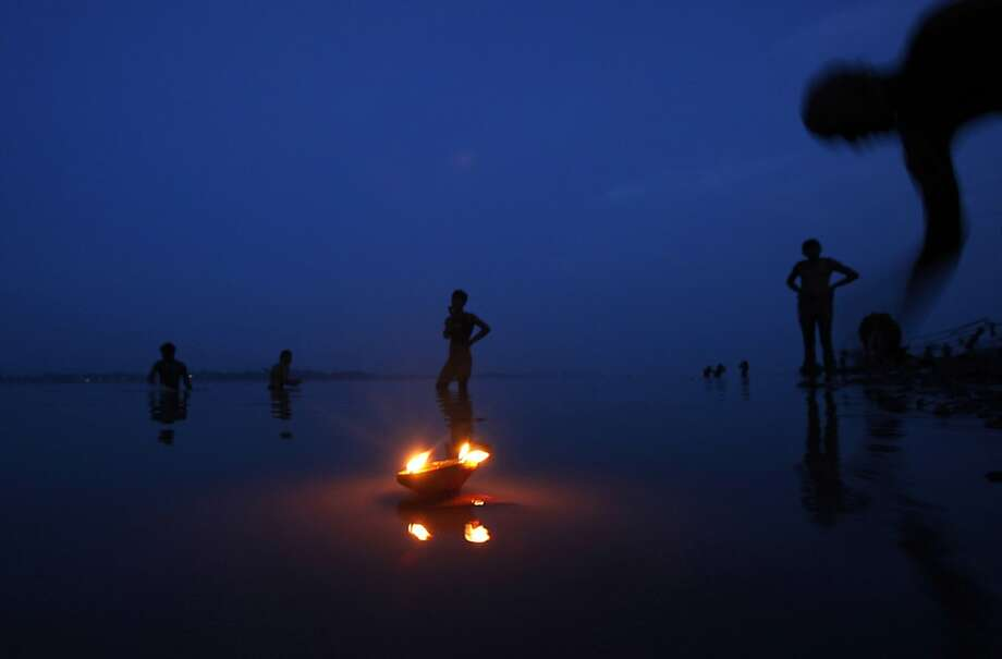 An oil lamp floats as devotees perform evening rituals on the River Ganges in Allahabad, India, Friday, Sept. 7, 2012.  Allahabad, at the confluence of the rivers Ganges, Yamuna and the mythical Saraswati, is an important Hindu pilgrimage center. Photo: Rajesh Kumar Singh, Associated Press