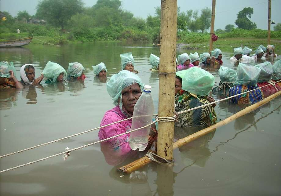 Villagers stand in neck-deep water in protest against the state government's move to increase water levels of regional dams causing flooding of their farmland, at Khandwa village of the central Indian state of Madhya Pradesh on September 6, 2012. The demonstrators, who have been protesting since August 25, claim that over  1,000 acres of land is already submerged with another 60 villages threatened to be submerged if the water level in the Omkareshwar dam is increased further. Photo: Strdel, AFP/Getty Images