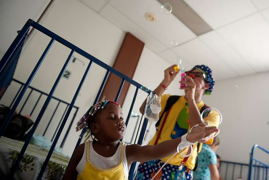 "Clowns cheer a little patient during a visit to the Hospital Universitario del Valle, on September 7, 2012, in Cali, Colombia, as part of the activities of the First National Congress of Hospital Clowns. The ""hospital clowns"" are health professionals who by means of laughter therapy try to lower the levels of stress of the inmates and to reduce their suffering. Photo: Luis Robayo, AFP/Getty Images"