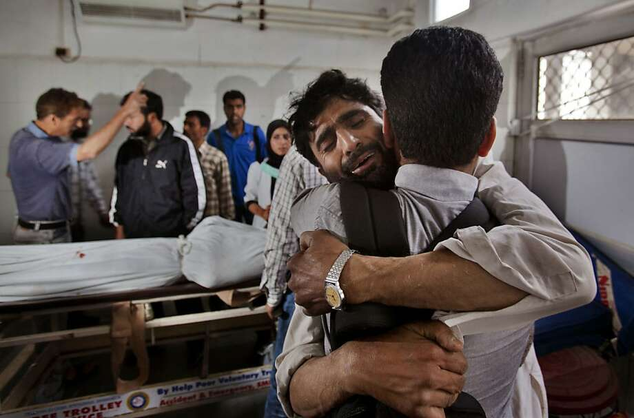 An unidentified man comforts a wailing relative of Ghulam Hassan Rather after identifying his body in Srinagar, India, Friday, Sept. 7, 2012. Two people died while 17 others were injured when a passenger bus skidded off the road in central Kashmir's Budgam district, according to a local news agency. Photo: Dar Yasin, Associated Press