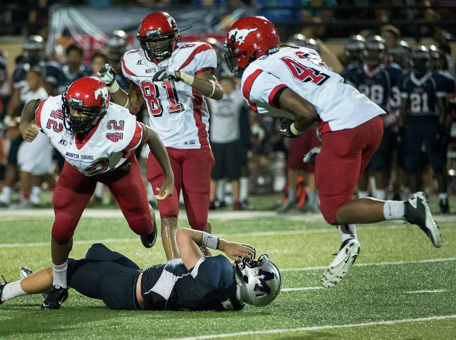 North Shore linebacker Christian Jacobs (42) celebrates with teammates Renaul Long (81) and Isaiah Freeman (48) after sacking Manvel quarterback Shane McCarley (3) in the second half. The Mustangs' defense held the Mavericks scoreless in the second half. Photo: Smiley N. Pool / © 2012  Houston Chronicle