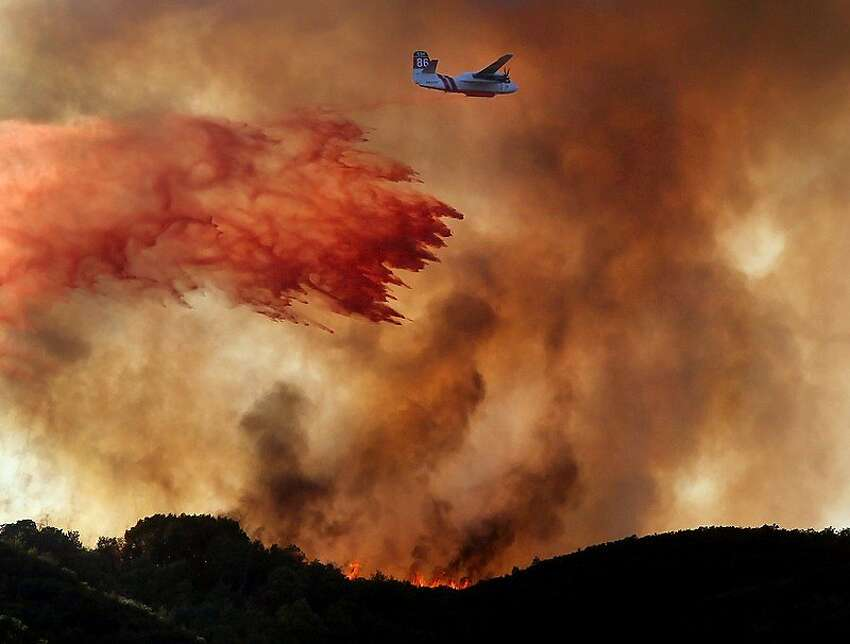 A Cal Fire air tanker drops a load of fire retardant across the head of the Scotts Fire above Scotts Valley in Lake County, Calif., Friday Sept. 7, 2012.