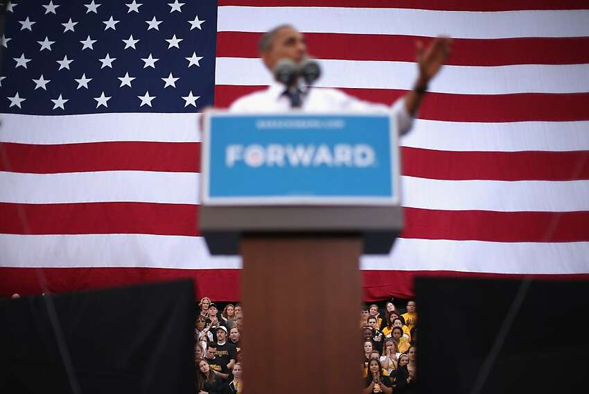 Supporters sit behind U.S. President Barack Obama as he addresses a campaign rally at the University of Iowa September 7, 2012 in Iowa City, Iowa. The president campaigned a day after accepting the nomination for president at the Democratic National Convention in Charlotte, North Carolina.