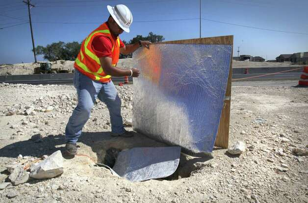 Eric Otero, Project Manager with TxDOT, removes thermal material protecting the climate in a small cave where endangered spiders were found after construction workers encountered the small cave while grading land along Texas 151 near Loop 1604 for an underpass.  Endangered spiders were found in the small feature, halting construction work as Biologist study the rare spiders  Friday, Sept. 7, 2012. Photo: Bob Owen, San Antonio Express-News / © 2012 San Antonio Express-News