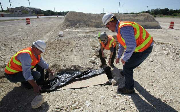 TxDOT workers Joshua Donat, left, Stirling Robertson, right, and Biologist Jean Krejca, center, inspect a small cave they found as construction workers were grading land along Texas 151 near Loop 1604 for an underpass.  Endangered spiders were found in the small feature, halting construction work as Biologist study the rare spiders  Friday, Sept. 7, 2012. Photo: Bob Owen, San Antonio Express-News / © 2012 San Antonio Express-News