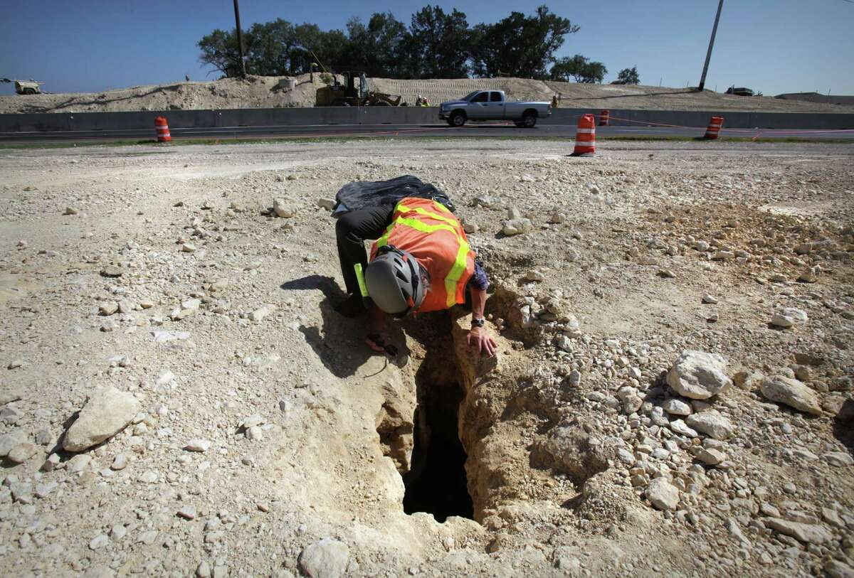 Biologist Jean Krejca inspects a small cave uncovered where TxDOT has been building an underpass on Texas 151 at Loop 1604. Work on the road project has been halted indefinitely.