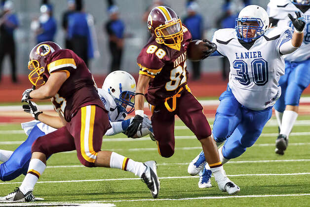 Harlandale's James Mendoza (center) slips between Lanier's Joesph Garcia (left) and Jesus Martinez as teammate Rudy De Los Santos throws a block en route to an 88-yard touchdown in the second quarter of their game at Harlandale Memorial Stadium on Sept. 7, 2012.  Harlandale won the game 58-16.  MARVIN PFEIFFER/ mpfeiffer@express-news.net Photo: MARVIN PFEIFFER, Express-News / Express-News 2012