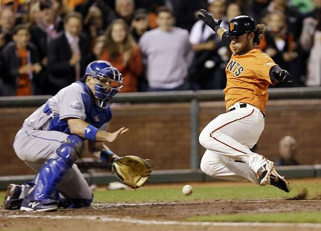 San Francisco Giants' Brandon Crawford, right, scores past Los Angeles Dodgers catcher A.J. Ellis on a bases-loaded single from Marco Scutaro during the seventh inning of a baseball game on, Friday, Sept. 7, 2012 in San Francisco. (AP Photo/Marcio Jose Sanchez) Photo: Marcio Jose Sanchez, Associated Press
