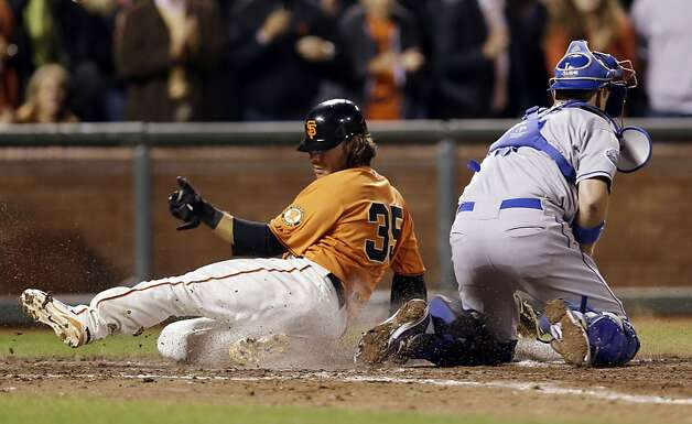San Francisco Giants' Brandon Crawford, left, scores past Los Angeles Dodgers catcher A.J. Ellis on a bases-loaded single from Marco Scutaro during the seventh inning of a baseball game on, Friday, Sept. 7, 2012 in San Francisco. (AP Photo/Marcio Jose Sanchez) Photo: Marcio Jose Sanchez, Associated Press