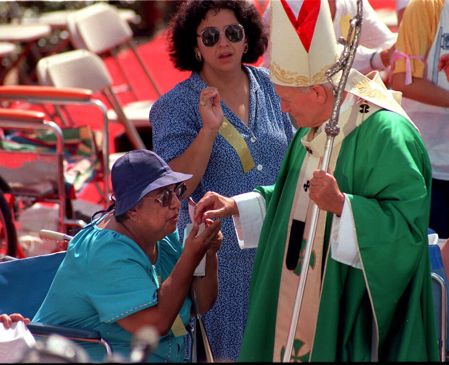 A woman kisses Pope John Paul's II hand before celebrating Mass at Westover Hills site Sunday, Sept. 13, 1987 during his visit to San Antonio. Photo: San Antonio Express-News File Photo / SAN ANTONIO EXPRESS-NEWS
